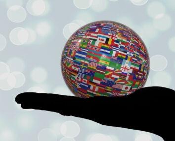 Ausgestreckte Hand im Schatten mit Ball in der Hand, welcher vollständig mit unterschiedlichen kleinen Landesflaggen bedeckt ist, als Symbol für die Vielfalt der Sprachen