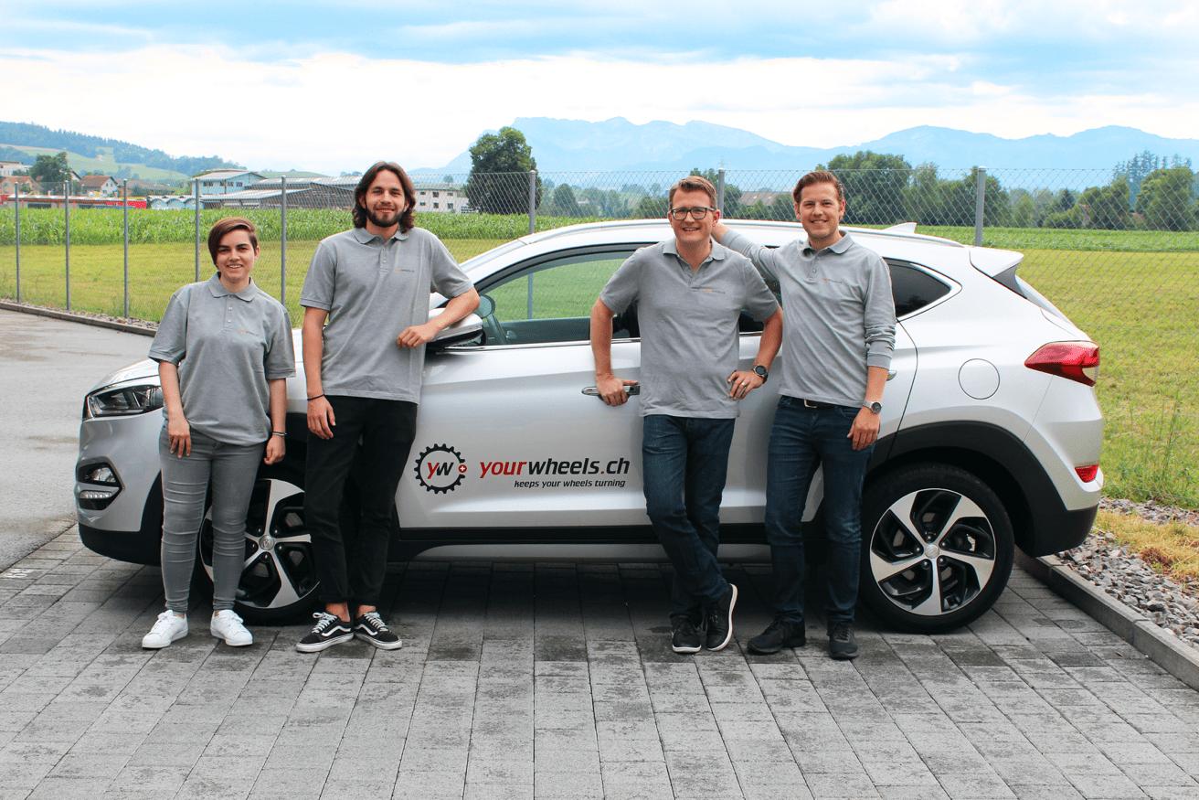 Yourwheels Team, 4 Personen vor einem Auto mit der Beschriftung Yourwheels