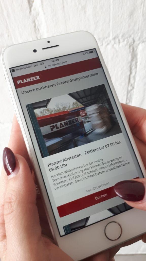Frau bucht einen Termin online über das Smartphone bei der Planzer Transport AG